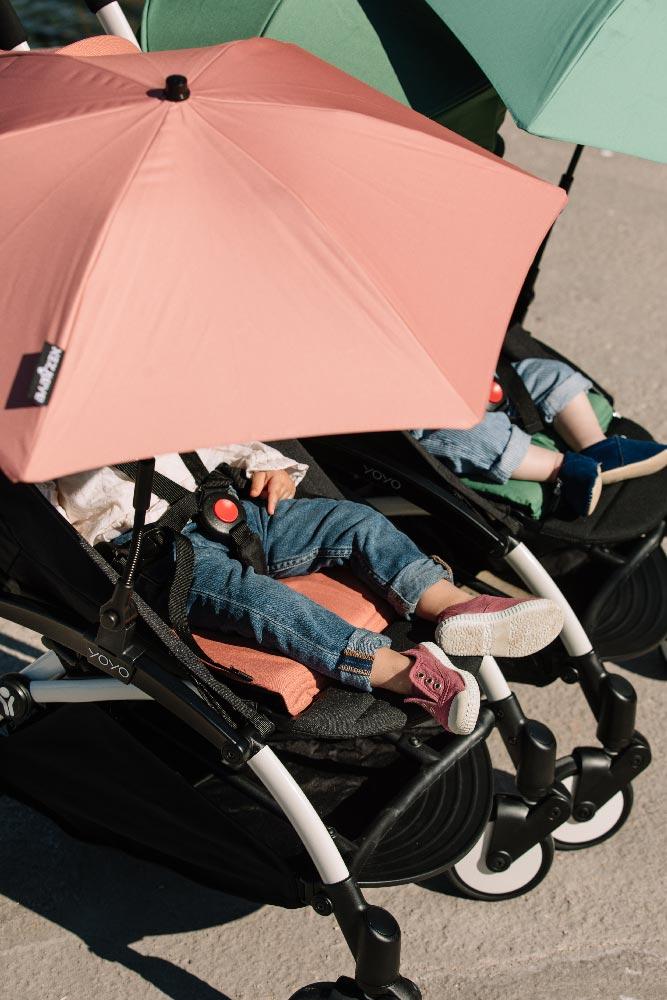 Zwei Kinder und rosa Sonnenschirm