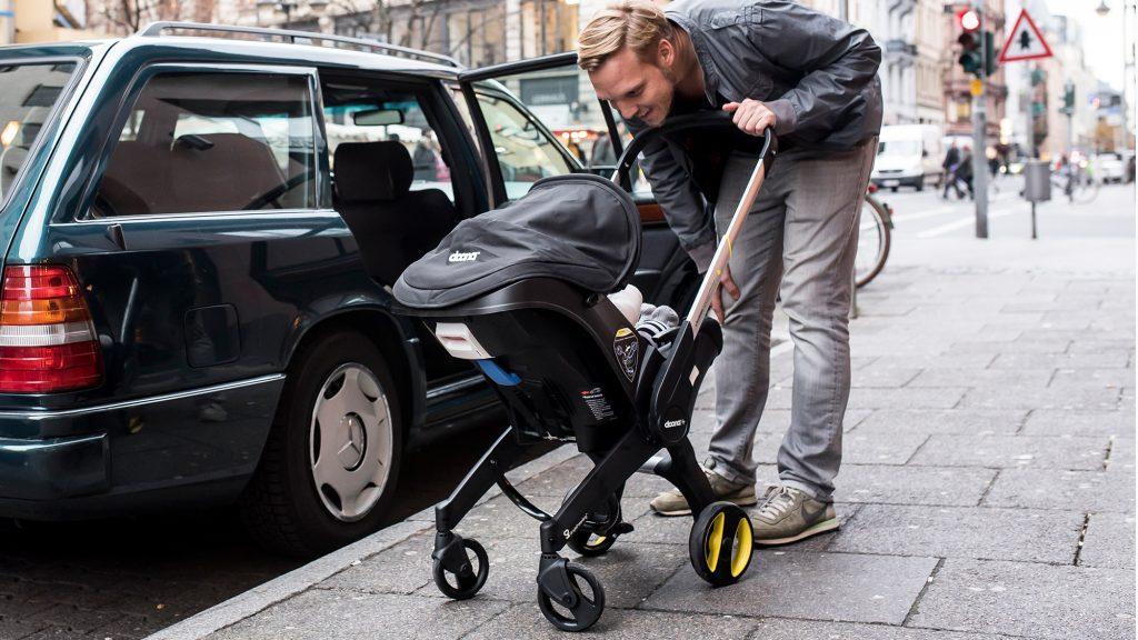 Vater mit Babyschale vor einem Auto.